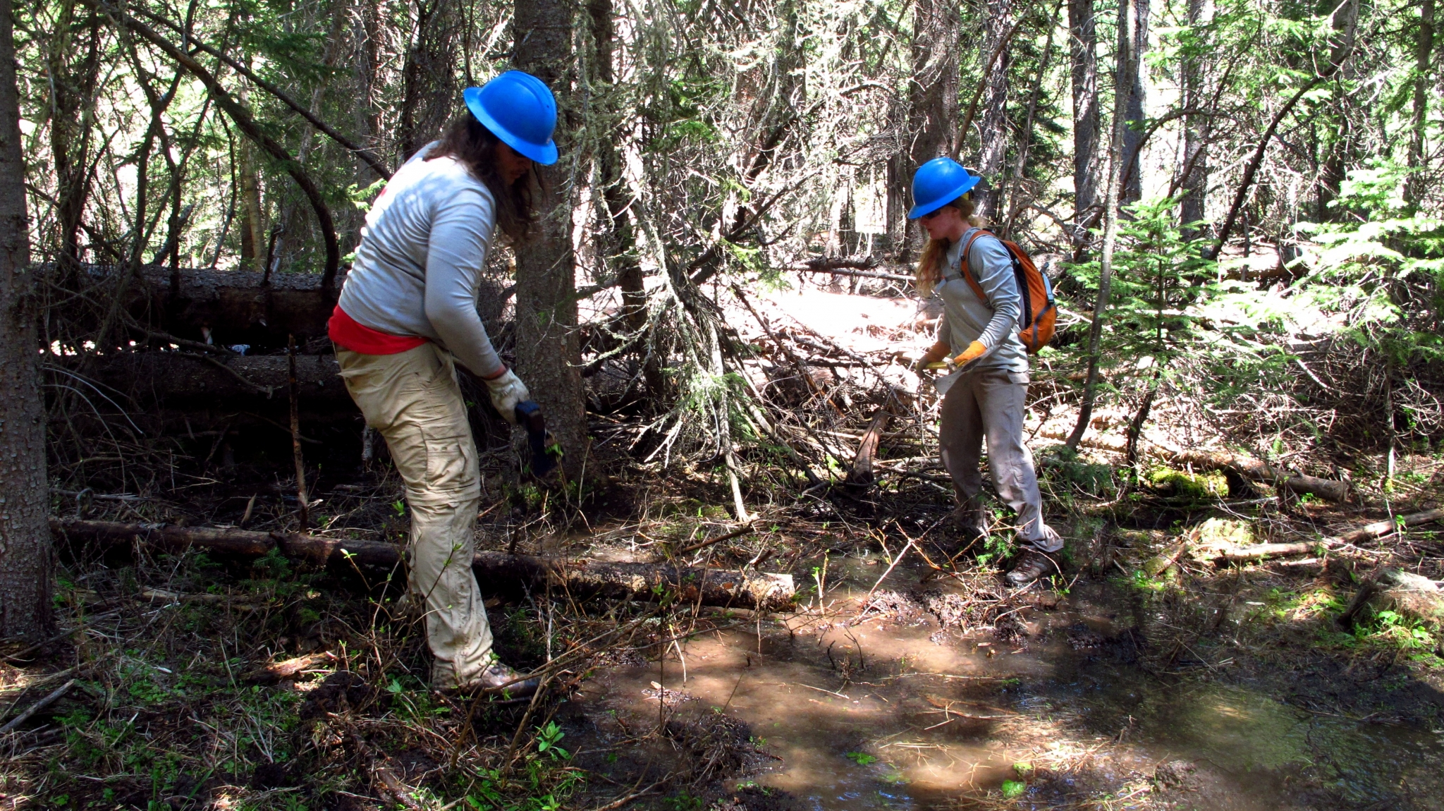 Tommy and Shelby digging a drainage to divert water from the trail.